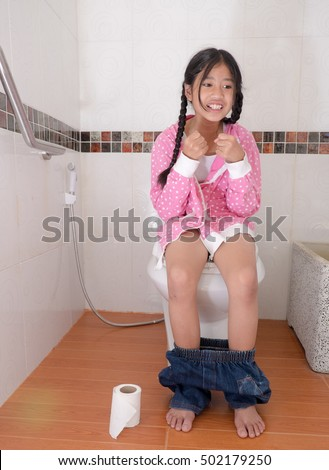 Girl sitting on toilet